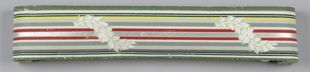 Thin multi-colored banding with interupted meandering white floral motif green end and silver center stripes on green ground. Matching ready-pasted border