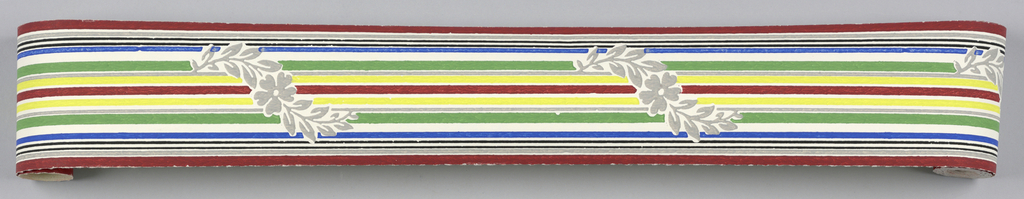 Red, gray, black, blue, green, yellow stripe with meandering gray foliate pattern on white ground. Matching ready-pasted border.