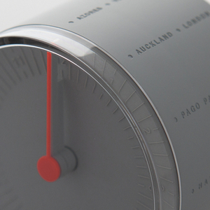 Circular clock face contained within a cylindrical body. The gray clock face features embossed numbers with gray hour and minute hands and an orange second hand. Twenty-four city names are debossed along the cylindrical body.
