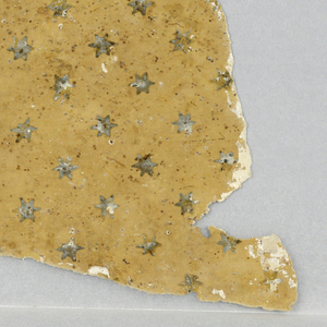 a) Powdering of six-pointed stars which are now black, having probably changed color from brown. Fragments of plaster indicate paper was plastered over. Joined sheets measure aproximately 19x22 inches; b) Swag border with pearls, flowers and foliage.