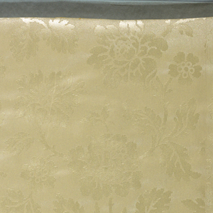 Imitation satin, lightly raised blossoms, branches and leaves; similar to decoupage. Shiny off-white on shiny off-white. There are two repeats to a width and the match is straight across. The design is a random arrangement of fair sized, twisting branches, leaves and blossoms.