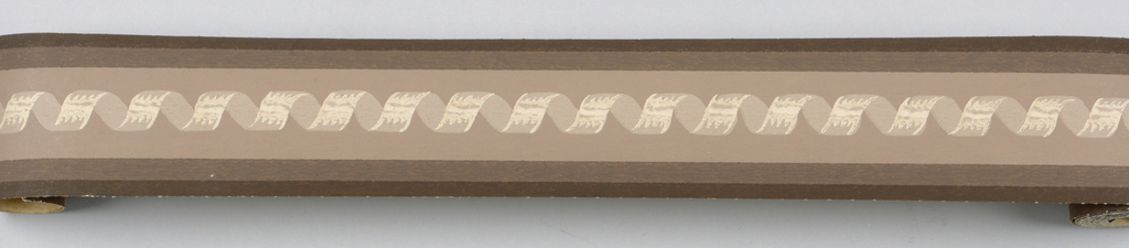 Central twisted ribbon motif in off-white with darkening shades of brown at edges on brown ground.