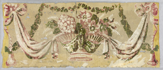 Central basket of flowers, draped fabric swags between basket and large bow knot, which connects to tassel or suspended bell. Printed in shades of pink, white and varnished green on a faded yellow ground.