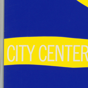 Abstract yellow design on bright blue background, printed white text on yellow band at lower portion of composition. Part of a series of posters commissioned to celebrate the 25th anniversary of the New York City Center.
