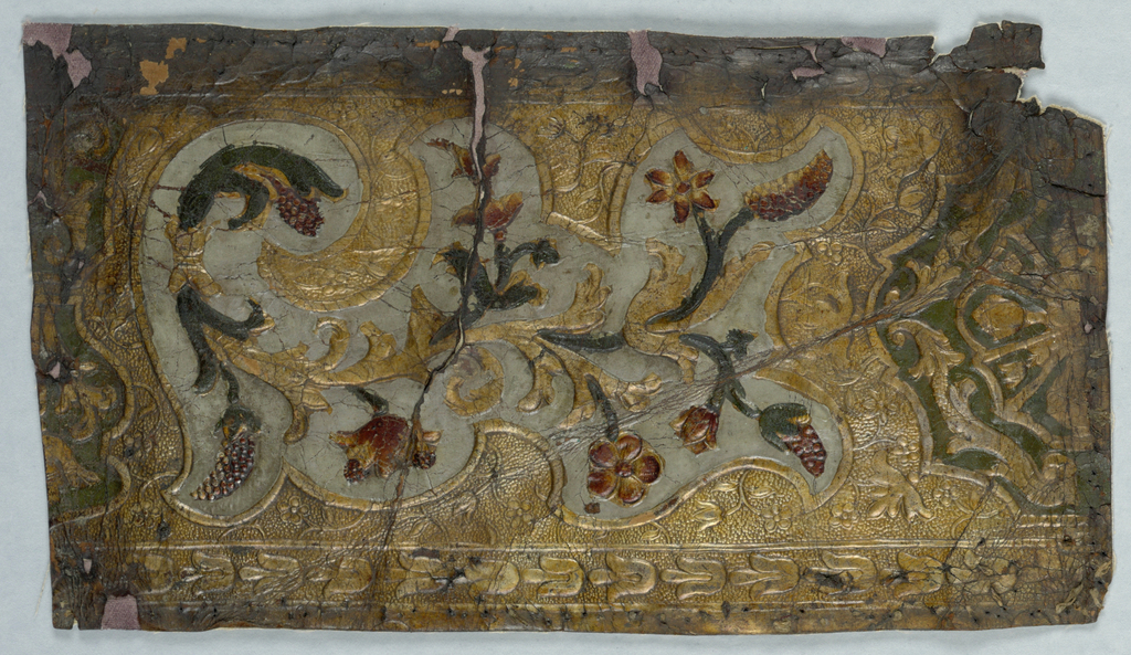 Scrolling vine with flower and fruit motifs, set within a cartouche, which alternates with another design. Bell flowers in band along edge.