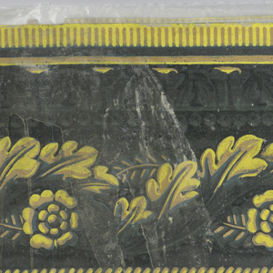 Wide central band of intertwined acanthus leaves, forming a guilloche-like design. Above this is ros of beading and tongue and leaf molding. Row of dentil motif along top edge with narrow band of cable molding or rope twist along lower edge. Printed in shades of yellow, ocher and gray on black ground.  H#556 ?