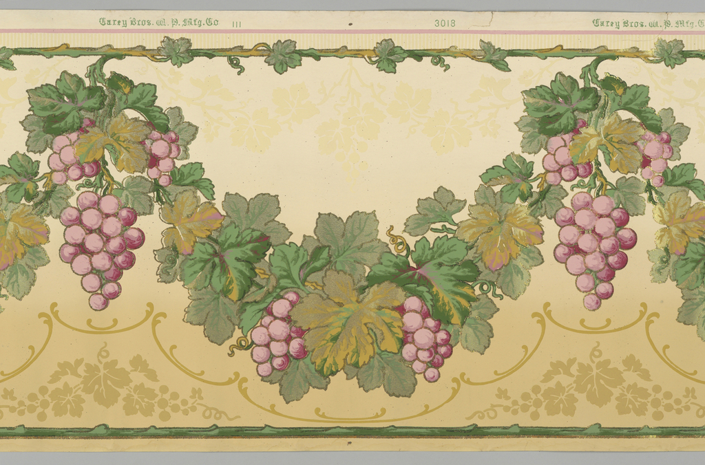 Flitter frieze with large swags of grapes and grape leaves, suspended from foliate band running along top edge. Printed in shades of green, metallic green, lavender,  tan and gold mica flakes on a background tan at bottom and lighter off-white at top.