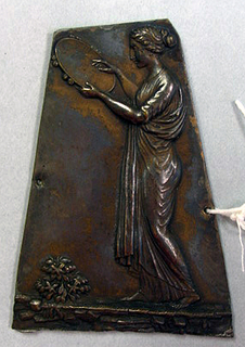 Irregular polygon. Draped female figure, stnading in profile facing left, with tambourine.