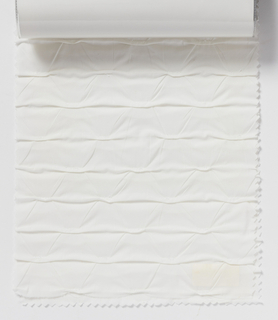 """Sample book with a photograph on the cover showing two lengths of """"Pacco"""" draped. Contains two samples of the fabric in the white colorway."""