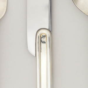 Rounded-rectangular blade inset into flat, long rounded-rectangular handle with raised-rounded border.