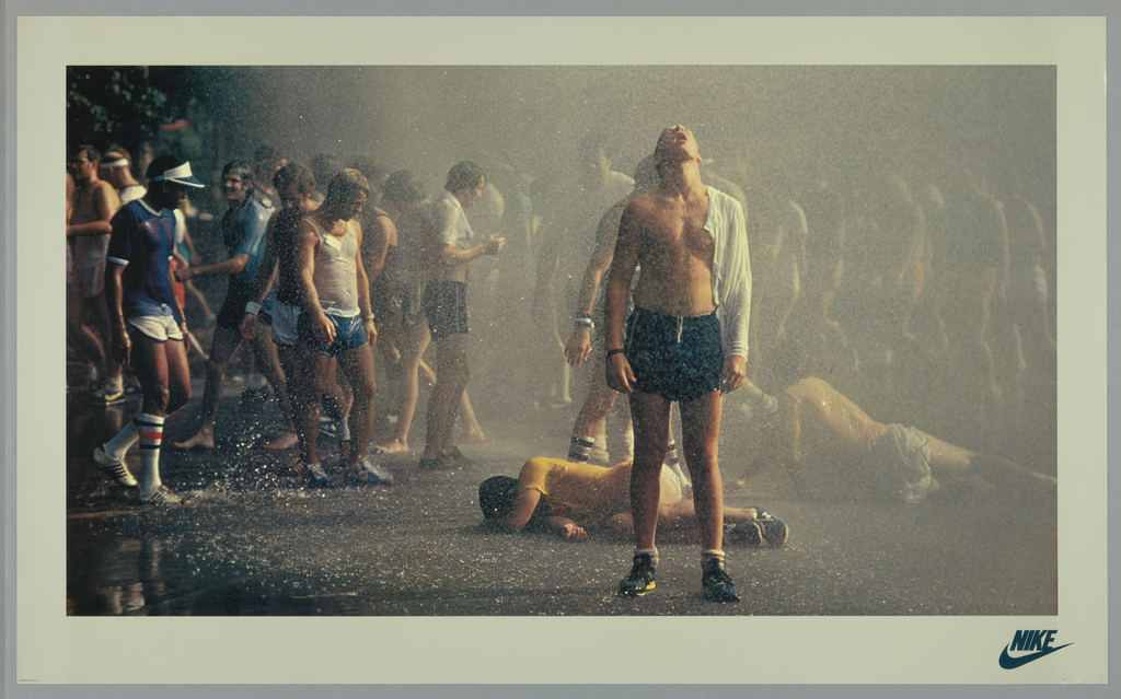 Poster featuring a color photograph of young male athletes standing, walking, and two are on the ground, in a torrent of rain. Lower right, in black: NIKE [with swoosh].