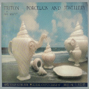 Poster for an exhibition or sale of the nautical-themed Triton collection designed by Arje Griegst and manufactured by the Royal Copenhagen Porcelain Manufactory. The poster depicts a dining service featuring ceramics resembling shells. The white ceramic objects are arranged in the foreground on top of sand, with an ocean visible in the background.The seascape also includes a blue sky filled with white clouds. Printed in black ink, left, upper margin: TRITON / BY / ARJE GRIEGST; across center and right, upper margin: PORCELAIN AND JEWELLERY.