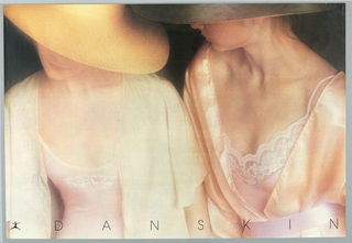 Horizontal rectangle. Color photoillustration in high contrast showing the upper bodies of two women wearing light pink leotards with white lace details, each covered with a silk shirt or robe and wearing a hat with a large brim that conceals most of their faces. Black background. Danskin graphic identity at lower left, a dancer with arms and legs outstretched. Printed text in black at bottom.