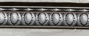 A band of egg motifs enframed in ovals of simplified foliage. At the bottom runs a band of elongated lozenges end-to-end. Printed in grisaille and tan on black ground.  H#364