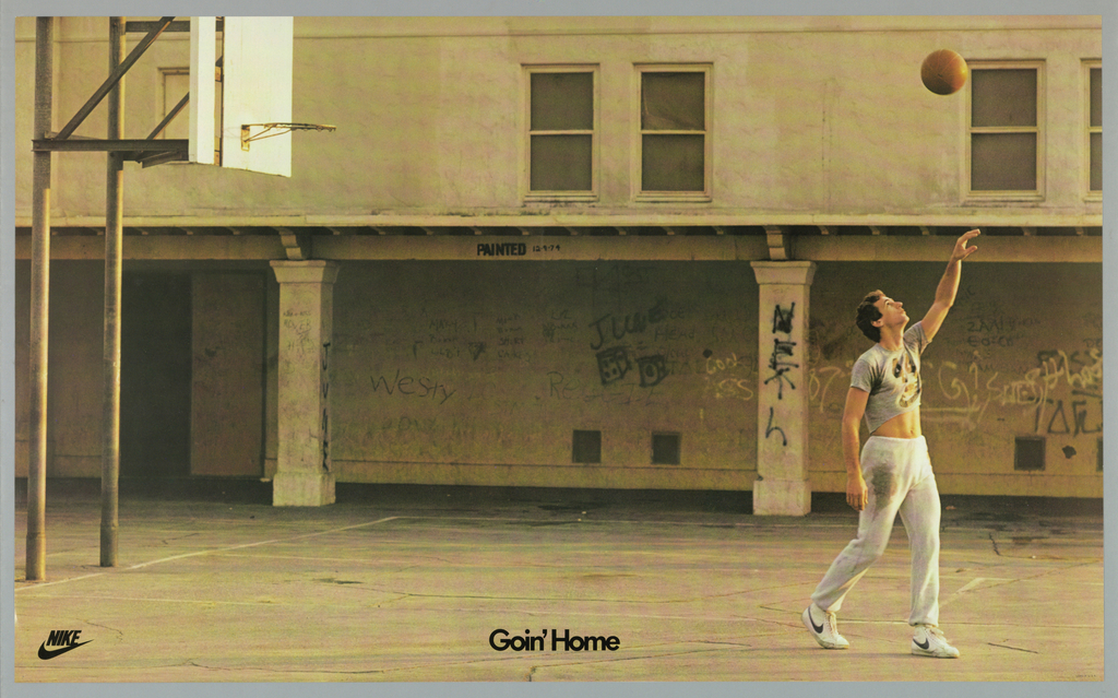 Photograph of a man, wearing grey sweats and white Nike sneakers, throwing a basketball in the air. He is in a basketball court with graffiti all over the walls. Lower right in black: NIKE [logo]; lower center: Goin' Home.