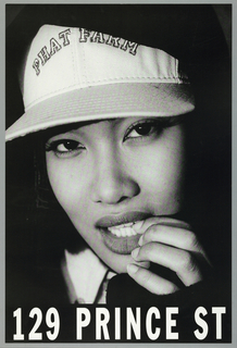 A woman's face emerges from shadows. She is wearing a white baseball cap with PHAT FARM in arching letters. She raises her hand to her mouth, as if to bite her nails. Below, in white block letters: 129 PRINCE STREET
