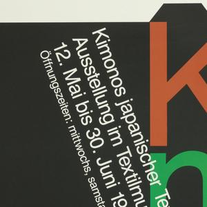 A black kimono with colored text: Ki / mo / no. In white ink, across kimono: Kimonos japanischer Textilkunstler / Ausstellung im Textilmuseum Max Berk, Heidelberg Ziegelhausen / 12. Mai bis 30. Juni 1991 / Offnungszeiten: mitwochs, samstags und sonntags von 13-18 Uhr.