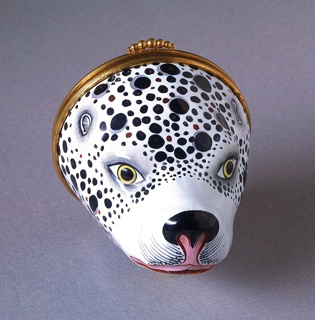 In shape of a Dalmation dog's head with hinged circular cover, thumb-lift of row of graduated beads. Cover slightly domed. Head is painted in naturalistic colors, spotted black on white ground, yellow eyes. Cover coarsely painted with standing Dalmation on paved terrace, trees beyond, surrounded by violet scrolls. Interior is white.