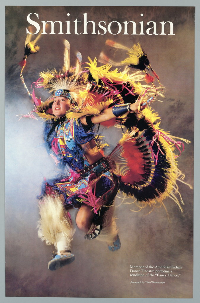 """Exhibition poster for American Indian Dance Theatre performance. Imprinted in white, across top: """"Smithsonian"""". Color photo reproduction of Native American male performing ritual dance called """"Fancy Dance"""".  His costume comprises of elaborate head dress (in yellow, black, red) reaching to his legs.  Teal beaded moccasins, head band, and belt.  Text explaining photography at lower right."""