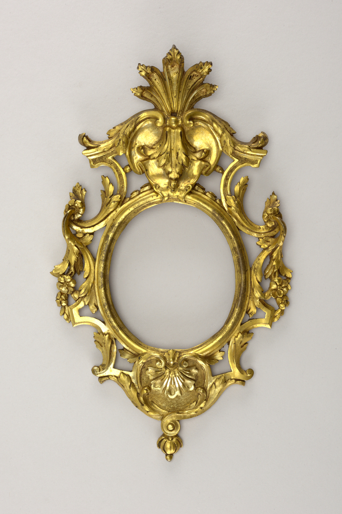 Frame pierced with palmette cresting and scroll-work of foliage; oval opening.