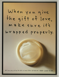 Photograph of a skin-colored condom with handwritten note: When you give / the gift of love, / make sure it's / wrapped properly.
