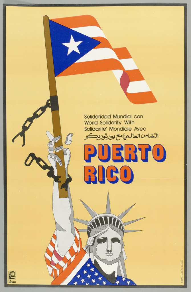 """Against yellow backdrop, Statue of Liberty draped in USA flag with upraised right arm holding Puerto Rican flag, with broken shackles. At center right, text reads in black """"World Solidarity with"""" in Spanish, English, French, and Arabic, and below in red text with blue shadow """"Puerto Rico."""" Logo of arm holding rifle under a globe appears in rectangle at lower left, with """"OSPAAAL"""" below."""