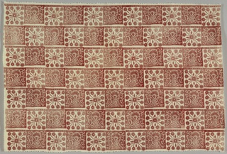 Design of alternate red and white squares with a stylized floral pattern.