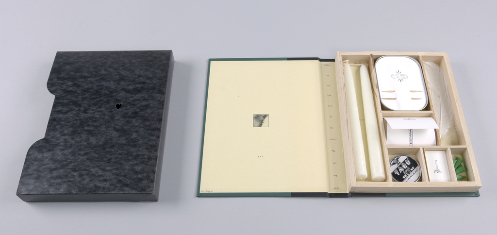 The box-shaped jacket, closed on three sides, is constructed of coated black, marbleized stock, notched on the edge in the center of the open side, front and back. There is an incised outline of a heart in the center, front.  Book, front and back covers: Dark green cloth; spine bound in black cloth, extending about two inches each onto front and back.   Front cover:  Imprinted in metallic gold, a heart, pierced on the diagonal by an upward-pointing arrow, is positioned underneath the incised outline of the jacket, through which the gold color is visible.  Spine: With the object laid flat, back cover down, A Romance is imprinted horizontally in gold lower case, the a italicized, the remainder in sans-serif type; with the object standing, M&Co/ Vol.4, imprinted just above the bottom edge, may be viewed.  Inside front cover: Within a centered square, outlined in black, is a photographic close-up facial view, aborted on all four sides, of the faces of a man and woman on the verge of kissing. Their eyes are closed and lips parted; on the left, the man is in front of the woman and in shadow; the woman emerges from shadow into bright light. About half-way down, directly underneath, yes is imprinted in miniature type.  Inner spine: A twelve-word quotation, one word per line, is imprinted top to bottom.  Inside back cover: An uncovered wooden box, fastened here, is divided into seven  sections, six of which are lined with beige paper, with one-word labels relating to the overall theme of romance, as well as to the specific contents; the seventh features a color illustration. On the left, spanning the full length of the box, a compartment holds two white tapered candles, their wicks attached. The word melt is imprinted on a curve in the center. In the upper half-length center section, labeled taste, a curve-sided tin is covered by white paper featuring two horseshoe shapes, their curves facing left and right, surrounding the word, oysters; three stylized electrical bolts jutting out top and bottom, complete the arrangement. Below this, two toothpicks, one underneath the other, are inserted in the paper cover. The top compartment in the lower center section holds a white envelope; the design is composed of an illustration in outline of two intertwined condoms (cover flap), a vertically positioned thermometer at low temperature (left inner flap), another thermometer at high temperature (right inner flap), and two packaged condoms (inside the envelope). The compartment lining shows a view of fireworks in white on a predominantly red background. The tripartite section beneath extends to the bottom and right edges: in the left compartment, labeled breathe, is a round tin of Tabu mints, an Italian brand; in the center, labeled spark, is a matchbox showing a log fire, curling upward; on the right, labeled burn, are four green incense pellets. The remaining compartment, labeled laugh, on the right and above the tripartite segment, holds a feather.