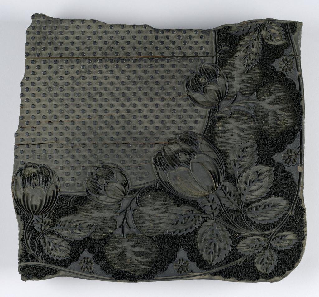 Block for printing textiles with a pattern of tulips and leaves arranged as a corner design. Carved wood and metal rods and strips set in the block create the design. In the field is a carved pattern of dots in diagonal rows. On the back of the block is hole, which probably held a handle.