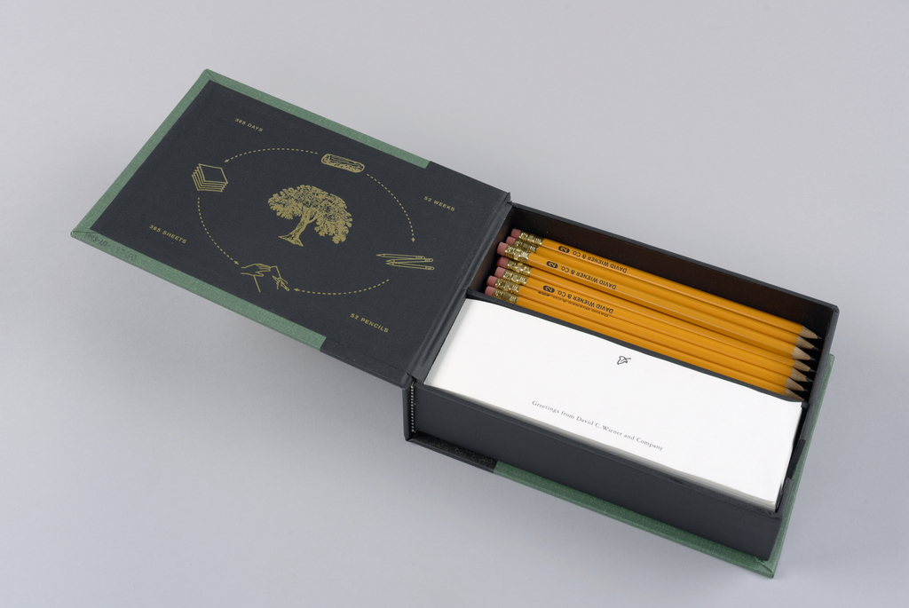 The box, which opens like a book, is fabricated in dark green cloth, with the spine bound in black cloth, extending about two inches onto the front and back. The front cover in imprinted in the center with an acorn design in metallic gold. With the object upright, David/ Wiener/ & Co. is imprinted on the spine in the top half; a design of a leaf, with stem, is imprinted just above the bottom edge.  Front cover, inside - The design, imprinted in metallic gold, consists of a tree in leaf, centered within an oval in dotted outline, which is interrupted at top center by a log; bottom center by a pair of hands, one resting and the other writing with a pencil on a sheet of paper; on the left side by a stack of paper; and on the right by three pencils. Outside the oval, 365 days is imprinted on the top left, 365 sheets on the bottom left, 52 weeks on the top right, and 52 pencils on the bottom right. A black opened box, divided in half horizontally, is clued to the inside back cover. The top half contains thirty-four yellow, sharpened No. 2 pencils, with red erasers, imprinted David Wiener & Co. in black capitals, adjacent to the eraser tip; and five red pencils, imprinted for use during week of April 15th in white capitals. N.b. Based on the presence of room remaining in the upper half of the box, as well as  the imprinting of the phrase, 52 pencils, it is conjectured that the original design indeed called for fifty-two pencils. The bottom half contains a stack of paper, imprinted at the top center in black with the same single leaf design appearing on the spine, and across the bottom, Greetings from David C. Wiener and Company.