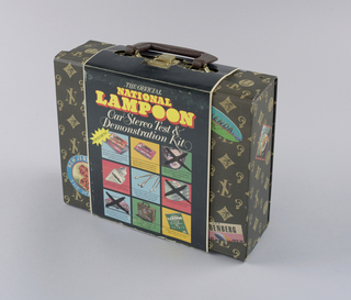 Wrapper - Folded around the center of the case, the wrapper design is imprinted on coated black cardboard.  Recto: The Official/ National/ Lampoon/ Car Stereo Test &/ Demonstration Kit fills the top third of the page. National Lampoon is imprinted in bubble type in yellow, shadowed by orange, and the ensuing two lines are italicized in white. Three rows of three squares each in varied pastel hues, separated by bars of the black background, occupy the remainder of the page. Within six of the squares are illustrations of the actual contents of the present object, each accompanied by explanatory copy imprinted below a thin black line: in row 1, left, cassette and plastic case, and center, head cleaner tape [missing]; row 2, left, bottle, and center, swabs; and row 3, center, travel case, and right, primer (instruction booklet) [missing]. Each of the remaining squares contains an illustration, on which a facsimile of a hand painted black X appears, of an item included in, but, of course, not actually part of, the kit, identified also by descriptive copy: row 1, right, a smiling young woman represents a date certificate; row 2, right, a stack of $1,000 bills represents four thousand dollars in cash; and row 3, a car represents a gift certificate for one. A jagged yellow shape containing the word, Including, in black is superimposed on the illustration in row 1, left. Verso: On a pale pea green background, the kit title is repeated on one line in a smaller version of the recto type. Copy appears in several lines at the top and bottom in the established humorous vein. In between, occupying most of the page is a list of the contents of the kit, along with prices. In the bottom right hand corner, a yellow oval, outlined in black, is imprinted A Steal At, followed by a $.              Case - The box style, dark brown faux leather travel case, furnished with a matching handle and fake brass fittings, is imprinted in a beige allover pattern composed of a monogram of the intertwined initials NL (National Lampoon) and three ideographs, a banana, its skin partially peeled, centered within a curved, four-sided figure; an ear; and two musical notes attached to a bar, within a circle. The design is a parody of the LV (Louis Vuitton) luggage pattern. Fake multicolored travel stickers are superimposed, five on top, four on bottom and one each of the sides. The program lampoons authentic historical travel sticker designs, features deliberate misspellings, and refers to real life transportation disasters, as well as contemporaneous advertising slogans and cultural mores. Some examples in detail: With a nod to Art Deco travel posters, within a rectangle bordered in pale green and against a salmon-colored background, a frontal view of a black steamship floats on white and black waves; grapes, a wineglass, a wine bottle and a baguette are in the foreground below; and Andrea/ Doria/ (in red and white capitals) Now That's Italian (in white on black) are imprinted above. Evoking an airline logo, a turquoise and green oval, divided horizontally by a red strip ending with an airplane in flight on the right, is imprinted Wallenda/ Airlines/ Come Fly with Us. The remaining stickers are labeled Club/ National/ Lampoon/ the Last Resort; New Jersey, the Pizza State; The/ Hindenberg/ When You're Hot, You're Hot; HMS/ Nobody Does It Better/ Titanic; Dante's/ Disco Inferno/ You Can't Stop the Music; Queen Bruce/ Transatlantic Cruising; Purdue/ Airlines/ The Wings, Breasts and/ Thighs of Man; Ganges Swim Club/ New Delhi; and Amelia and Werner/ Earhart/ Airlines/ If We Disappear It's/ Your Responsibility/ AWEA.   Inside, the case lining, also in dark brown, is fitted with two rows of slots, ten per side, to accommodate audiocassette tapes within plastic cases. A channel divides the two rows.   Audiocassette tape - Located in one of the slots, the tape's interior label displayed along the narrow top edge of the clear plastic case reads The Official National Lampoon Car Stereo Test & Demonstration Tape. The whole continues the spoof introduced on the case exterior. Recto: Headed Official License [and] Registration, the fake identifying document, a license to play the enclosed tape on a car stereo, spells out the conditions for doing so, and displays a faux signature, Jerry Taylor, undersigned Gerald L. Taylor/ Commissioner of Audio Vehicles.  The remaining contents, ostensibly for cleaning tape player heads, are a package of cotton swabs labeled Official National Lampoon Car Stereo Test and Demonstration Kit Cotton Swabs and a bottle, now empty, of similarly labeled clear fluid. Explanatory language on both continues to spoof consumer advertising.