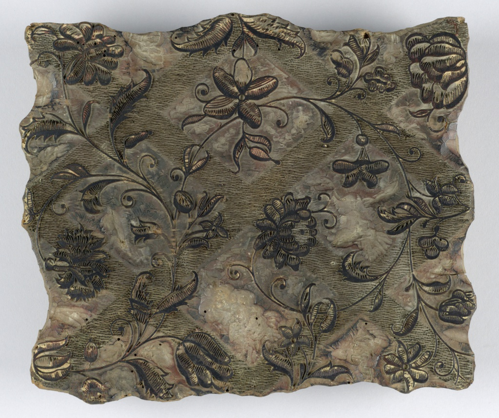 Wood block with metal pins for printing textiles. Design of curving fine branches with large blossoms and leaves in raised wood. Background of lozenge-shaped areas set off by wide lines of dots, each dot being a tiny metal pin.