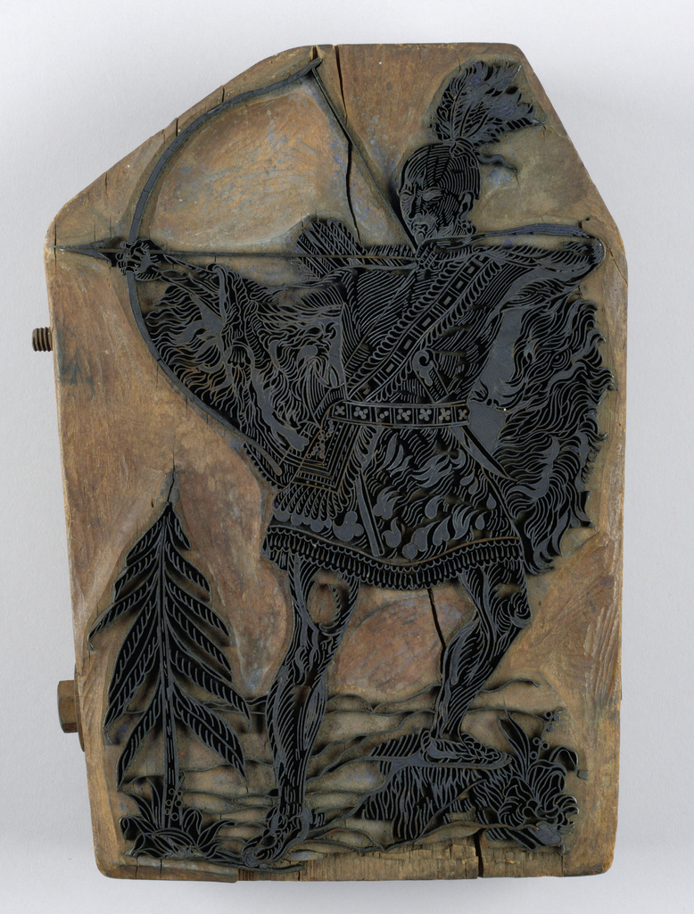 Printing block with copper insets. Design shows warrior with pulled arrow, tree and mountains in the background. Used as a bale block for marking sacks and ends of bolts of cotton fabric.