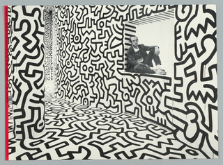 Recto: Black and white photographic image of Keith Haring seated in a window niche of the Pop Shop in New York City. The floors, walls and ceiling are covered inin Haring's black line intersecting figure motifs. Verso:Photographic montage of the items available for purchase at the Pop Shop. Includes T-shirts, pillows, stickers, magnets, etc. The image is dominated by a young black man wearing a t-shirt with the crawling baby logo. Small children are at left and right. The elements are superimposed over a red line drawing by Keith Haring.