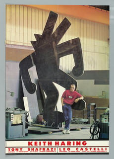 Color photograph of the artist in a sculpture fabrication studio. Haring, wearing blue jeans and a red -shirt with crawling baby logo, leans against a large, steel sculpture of a dancing dog. In red block letters below image on white border, KEITH HARING.