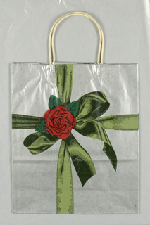On silver background, green ribbon with rose, as though bag was gift wrapped.