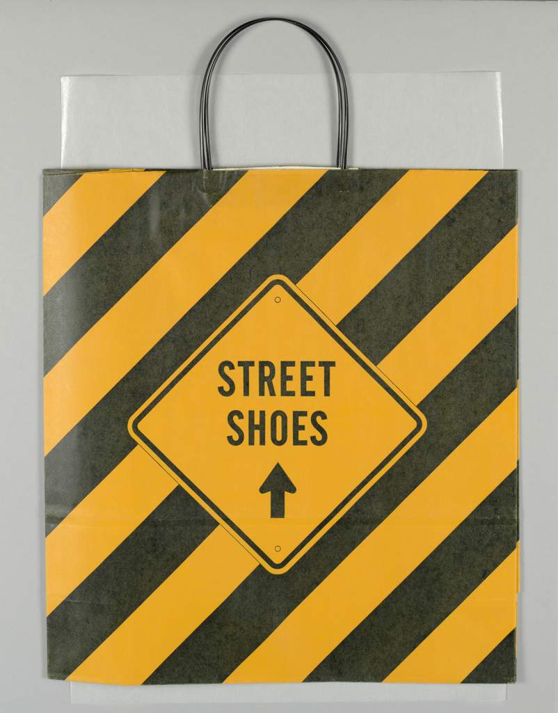 Alternating black and orange diagonal stripes over all. In center of recto and verso: a diamond shaped lozenge resembling a street sign is shown with the words STREET SHOES, and a black arrow below pointing up.