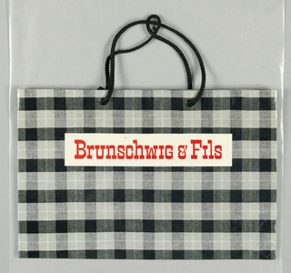 """Brunschwig & Fils"" in red on black, white, and gray plaid background."