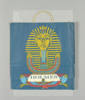 "Museum exhibition bag. Recto:  Blue, red, and gold illustration of head of  Tutankhamun; ""HOLMES"" in teal on white.  Side panels: ""Treasures of Tutankhamun"", with vertical columns and repeat of ""Holmes"" at bottom."