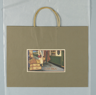 """1930s/40s-style design of man, woman, and porter, seen from neck down, walking  on railroad station platform with luggage. Text and image on horizontal sticker adhered to matte finish taupe bag. """"MH/ Marley Hodgson/ Ghurka Original Collection"""" on illustration of seal incorporated in design."""
