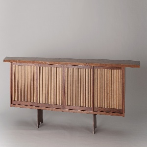 Long horizontal wooden cabinet; front composed of four large sliding rectangular doors with vertical slats over woven pandana panels; roughly rectangular top with irregular edges extending over cabinet front and sides; two plank feet, notched on bottom edge.