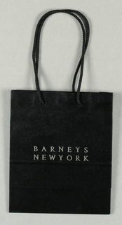 """BARNEY'S"" in metallic silver, centered in the lower part on  a black background."