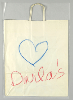 White paper bag with design on one side only; blue heart drawn in actual children's crayon at center; store name in red  crayon script font below.