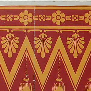 Textile imitation, wide zig-zag or herringbone pattern with suspended anthemia and tassels. Narrow band of floral motifs across top edge.  Printed in ocher and rust-color.  H# 461