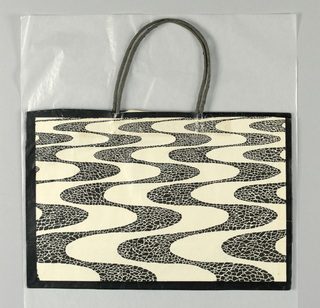 "Black with vertical undulating line pattern, based on sidewalks designed by Burle Marx at Copacabana, Rio de Janeiro.  Side panels: ""Brasil Fortnight."""