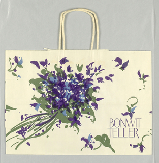"""White matte finish paper with purple, blue, and green scattered bouquets of violets and leaves.  """"BONWIT TELLER""""  in purple, lower right."""
