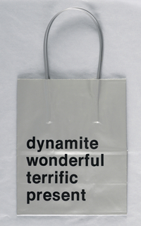"""Dynamite/Wonderful/Terrific/Present"" in print on silver background. Base: Jamie Ostrow, 419 Lafayette St., NY 10003. Price sticker: ""He Who Eats Mud."""