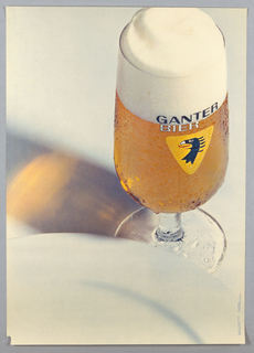 Extremely large closeup of a color photographic reproduction of a glass of beer fills right side of sheet. The Ganter logo (yellow triangle with stylized eagle's head) visible on glass. The rim of a white plate cuts a semi-circle across the lower one-quarter of sheet. Brown and yellow reflection at left center.