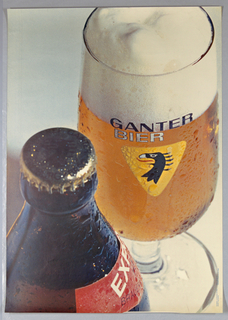 Extremely large closeup of a color photographic reproduction of a glass of beer. The glass bears the Ganter logo (yellow triangle with stylized eagle's head) and fills the right side of the sheet. At left an unopened brown beer bottle with a red label. The moisture on the surfaces of the glass and bottle is prominent.