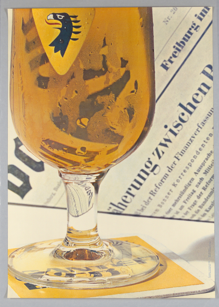 """Extremely large closeup of a color photographic reproduction of a glass of beer with logo of Ganter Beer (yellow triangle with stylized eagle's head) placed on a yellow and white coaster with blue newspaper text behind. The glass fills most of the left portion of the sheet. Moisture drooplets are shown in enlarged detail. The partially visible newsprint at right reads '...zwischen..."""""""